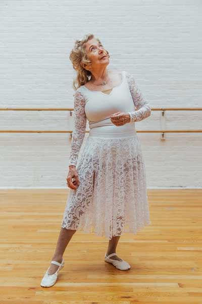 Mona poses in white lace ballet costume