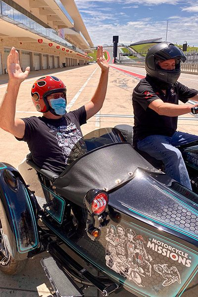 David with his hands raised enthusiastically as he rides in side car